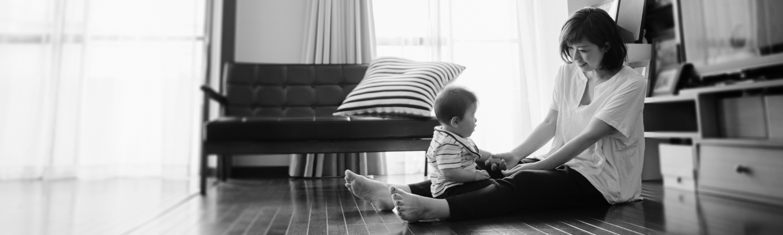 A mother sits on the wooden floor of her home with her young child.