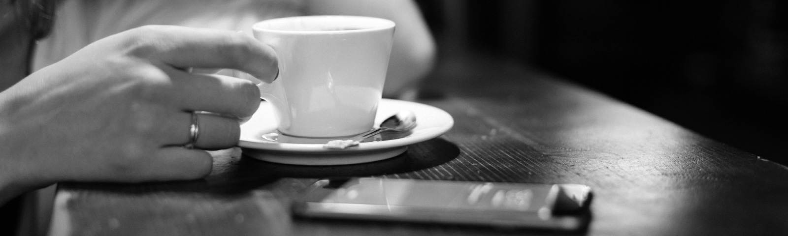 A woman's hand holding the handle of a tea cup in a cafe with her phone sitting nearby.