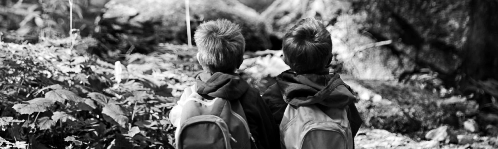 Two kids sitting outside looking into the woods with backpacks on.